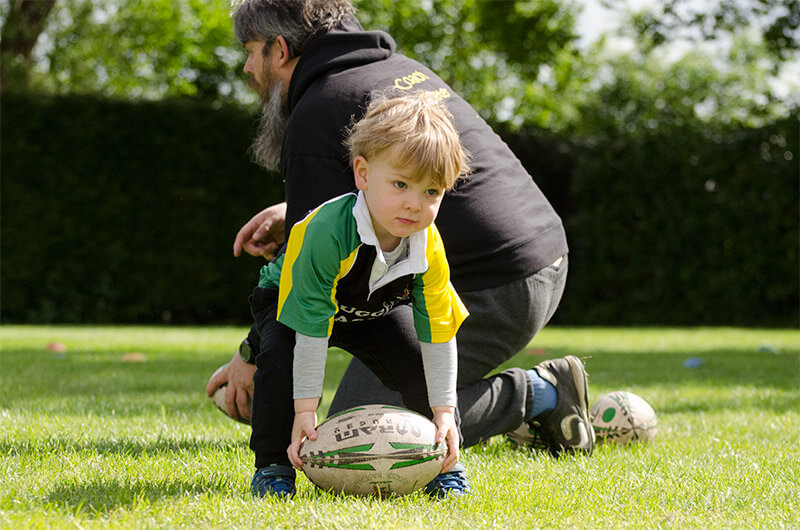 little boy pulling a rugby ball from the grass
